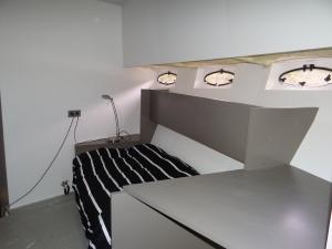 Zit/slaapbank in gastenkamer. Ruglening wordt een matras die omhoog kantelt tot stapelbed.